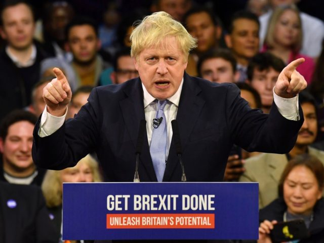TOPSHOT - Britain's Prime Minister and Conservative party leader Boris Johnson speaks during a general election campaign rally in East London on December 11, 2019, the final day of campaigning for the general election. - Britain will go to the polls tomorrow to vote in a pre-Christmas general election. (Photo …