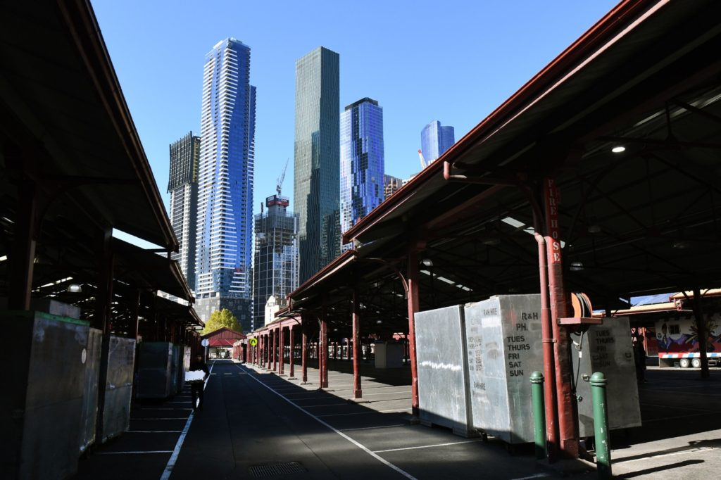A man (L) walks through a deserted part of Melbourne's Queen Victoria Market. Australia's economy is losing four billion Australian dollars (2.5 billion USD) every week its virus shutdown continues, while a million workers have already lost their jobs in the crisis. (WILLIAM WEST/AFP via Getty Images)