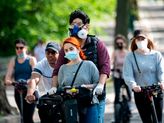 People wearing masks ride a scooter in Central Park on May 16, 2020 in New York City, amid the coronavirus pandemic. (Photo by Johannes EISELE / AFP) (Photo by JOHANNES EISELE/AFP via Getty Images)
