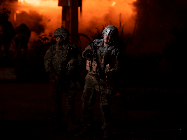 Members of the National Guard hold a perimeter as a fire crew works to put out a fire at a gas station on Lake Street on May 29, 2020 in Minneapolis, Minnesota. Protests have been ongoing in the state and around the country since George Floyd's death while in police …