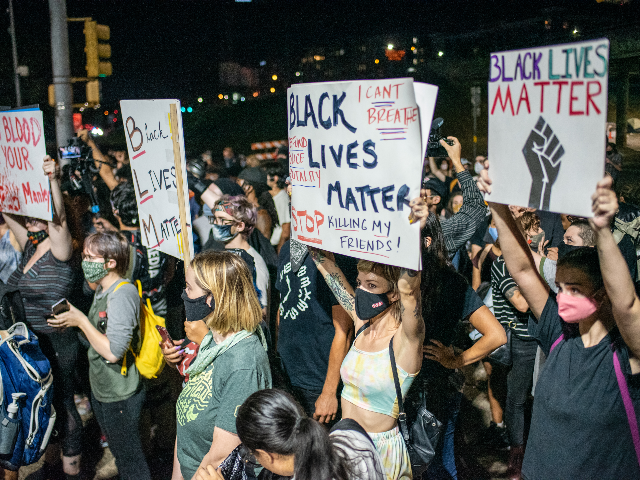 People hold up signs outside Austin Police Department after a vigil for Garrett Foster on July 26, 2020 in downtown Austin, Texas. Garrett Foster, 28, who was armed and participating in a Black Lives Matter protest, was shot and killed after a chaotic altercation with a motorist who allegedly drove …