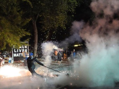 PORTLAND, OR - JULY 30: A protester flees as a flashing grenade explodes behind him during a protest against racial injustice and police brutality in front of the Mark O. Hatfield U.S. Courthouse in the early hours of July 30, 2020 in Portland, Oregon. Protests against the federal presence in …