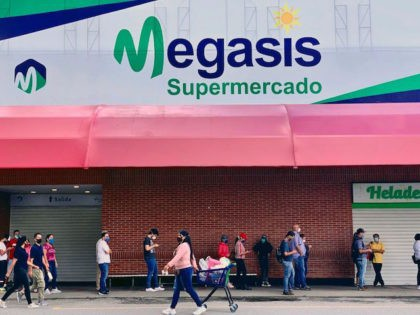 "People wear face masks as a preventive measure against the spread of the novel coronavirus, COVID-19, as people queue outside ""Megasis,"" the first Iranian supermarket in Venezuela, in Caracas on July 31, 2020. - The relationship between Tehran and Caracas is growing, challenging their common enemy, the United States. First, …"
