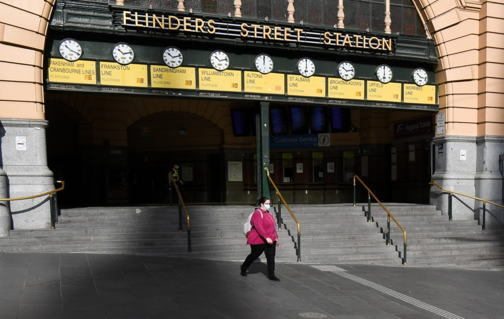 A woman walks out of a near-deserted Flinders Street Station in Melbourne in August 3, 2020 after the state announced new restrictions as the city battles fresh outbreaks of the COVID-19 coronavirus. Australia's Victoria state imposed fresh, sweeping restrictions on August 2, 2020, including a curfew in Melbourne for the next six weeks, a ban on weddings, and schools and universities going back online in the coming days. (WILLIAM WEST/AFP via Getty Images)