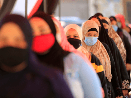 Egyptians wearing face masks against Covid-19 queue up to vote on August 11, 2020 for a new senate in an upper house election. - The two-day vote for 200 of the Senate's 300 seats will be largely contested by candidates who back President Abdel Fattah al-Sisi, who has quietened most …