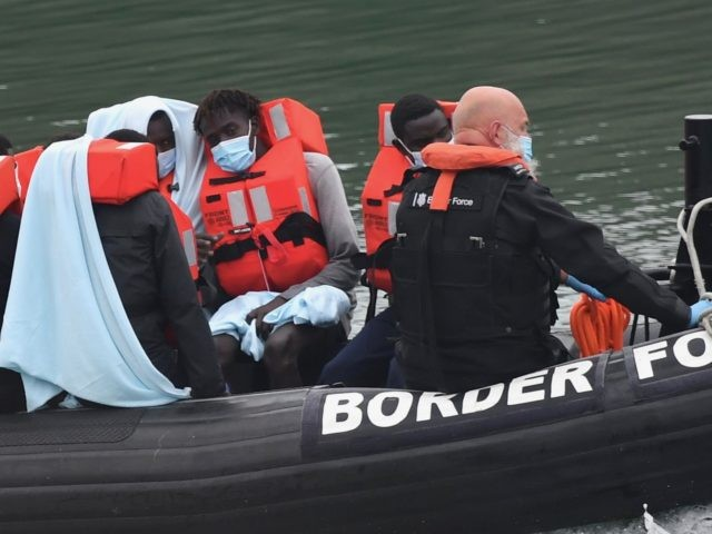 UK Border Force officials transfer migrants in a Patrol Vessel after they were intercepted while travelling in a RIB from France to Dover, at the Marina in Dover, southeast England on August 14, 2020. - British Prime Minister Boris Johnson on Monday said illegal migrant crossings of the Channel, which …
