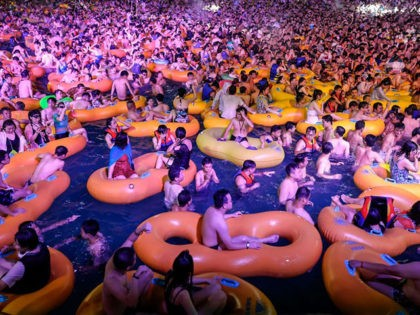 TOPSHOT - This photo taken on August 15, 2020 shows people watching a performance as they cool off in a swimming pool in Wuhan in China's central Hubei province. (Photo by STR / AFP) / China OUT (Photo by STR/AFP via Getty Images)