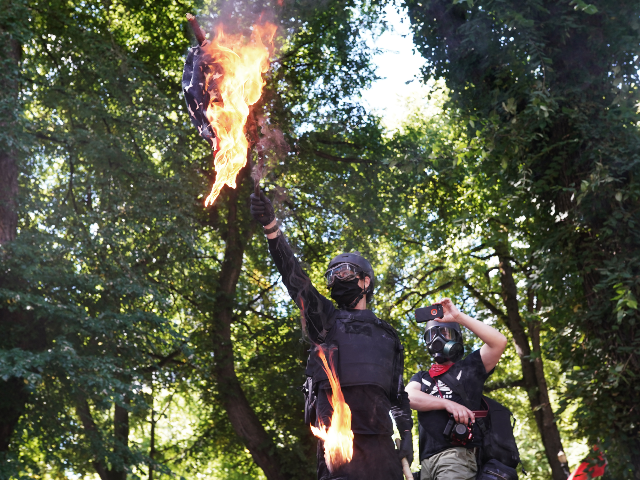 Anti-police protesters burn an American flag while facing off with right wing groups in front of the Multnomah County Justice Center on August 22, 2020 in Portland, Oregon. For the second Saturday in a row, right wing groups gathered in downtown Portland, sparking counter protests and violence. (Photo by Nathan …