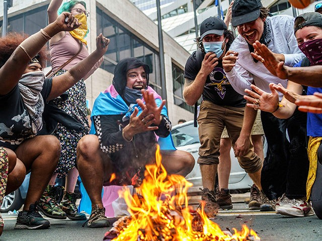 Protesters set fire to an US National flag outside theHennepin County Government Plazaduring a demonstration against police brutality and racismon August 24, 2020 in Minneapolis, Minnesota. - It was the second day of demonstrations in Kenosha after video circulated Sunday showing the shooting of Jacob Blake -- multiple times, in …