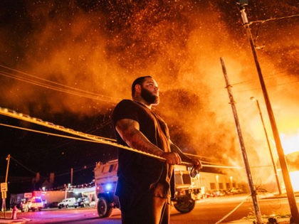 KENOSHA, WI - AUGUST 24: A man looks over caution tape during a second night of rioting on August 24, 2020 in Kenosha, Wisconsin. The civil unrest occurred after the shooting of Jacob Blake, 29, on August 23. Blake was shot multiple times in the back by Wisconsin police officers …
