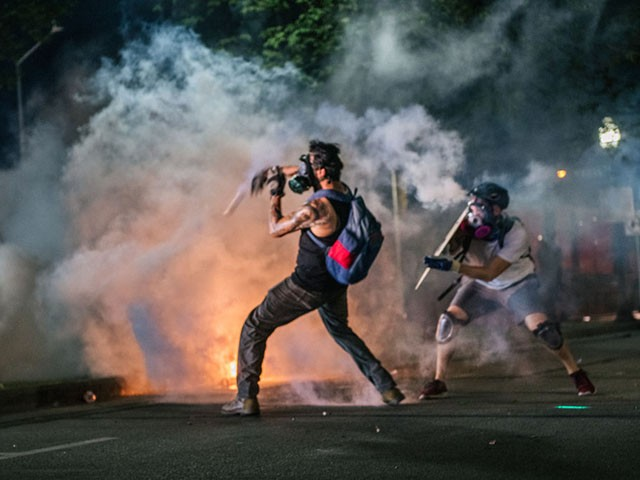 KENOSHA, WI - AUGUST 24: Demonstrators throw tear gas back at law enforcement on August 24, 2020 in Kenosha, Wisconsin. Additional law enforcement were deployed to protect the courthouse. Civil unrest occurred after the shooting of Jacob Blake, 29, on August 23. Blake was shot multiple times in the back by Wisconsin police officers after attempting to enter into the drivers side of a vehicle. (Photo by Brandon Bell/Getty Images)