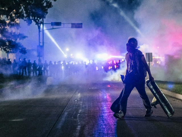 A demonstrator carries a make-shift shield across the street on August 25, 2020 in Kenosha, Wisconsin. As the city declared a state of emergency curfew, a third night of civil unrest occurred after the shooting of Jacob Blake, 29, on August 23. Video shot of the incident appears to show …