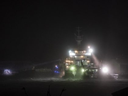 A picture taken on August 27, 2020 shows a ship anchored to a dock using a searchlight to look at smaller fishing ships as hurricane Laura passes over in Lake Charles, Louisiana. - Hurricane Laura slammed into the southern US state of Louisiana on August 27 and the monster category …