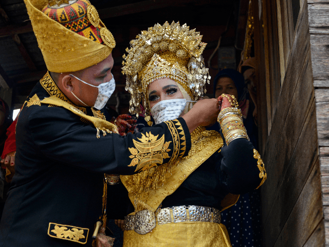 A newly-wedded couple put on face masks during a traditional wedding at a village in Lhoknga, Aceh province on August 30, 2020. (Photo by CHAIDEER MAHYUDDIN / AFP) (Photo by CHAIDEER MAHYUDDIN/AFP via Getty Images)