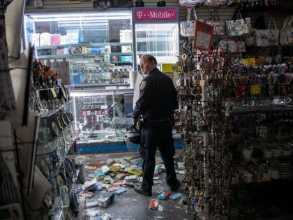 NEW YORK, NEW YORK - JUNE 2: A New York City police officer stands guard in a looted souvenir and electronics shop near Times Square after a night of protests and vandalism over the death of George Floyd early June 2, 2020 in New York City. Protesters took to the …
