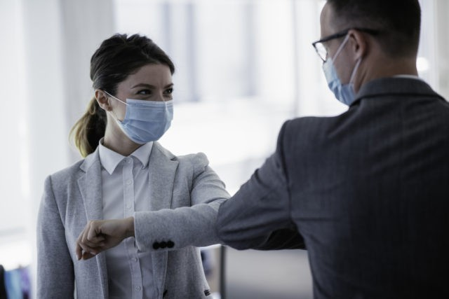 Businessman and businesswoman with medical mask in office.
