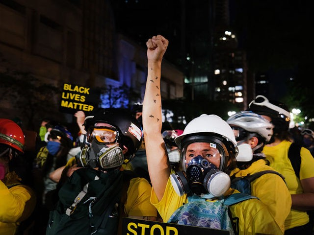 PORTLAND, OREGON - JULY 28: People gather in protest in front of the Mark O. Hatfield federal courthouse in downtown Portland as the city experiences another night of unrest on July 28, 2020 in Portland, Oregon. For over 57 straight nights, protesters in downtown Portland have faced off in often …