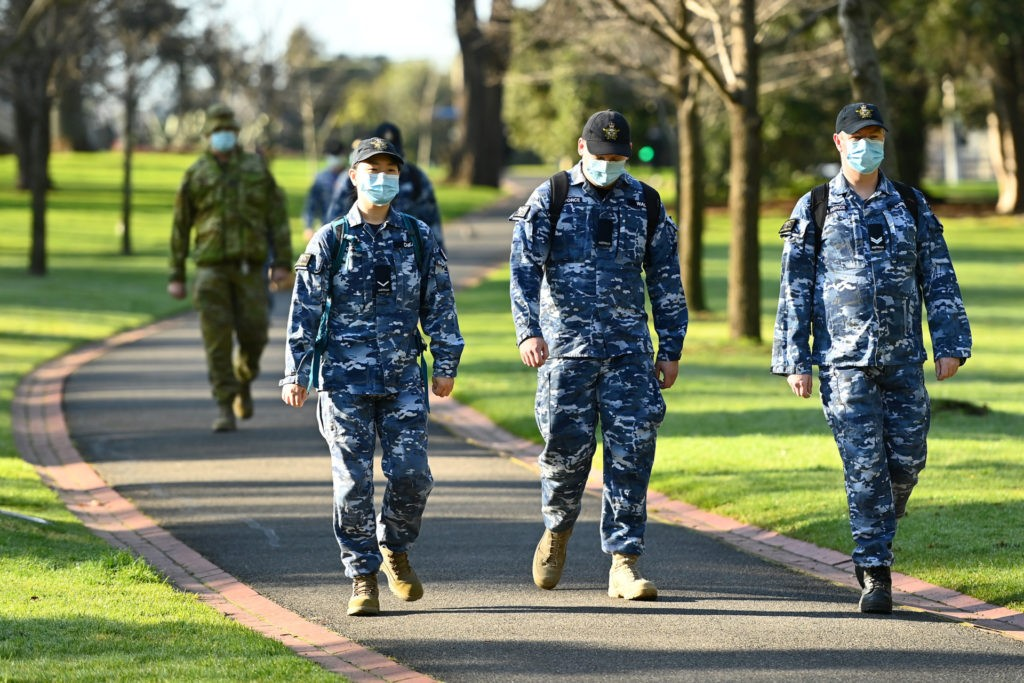 Members of the Australian Defence Force walk through Fitzroy Garden in Melbourne, Australia. Metropolitan Melbourne is under stage 4 lockdown restrictions, with people only allowed to leave home to give or receive care, shopping for food and essential items, daily exercise and work while an overnight curfew from 8pm to 5am is also in place. The majority of retail businesses are also closed. (Quinn Rooney/Getty Images)