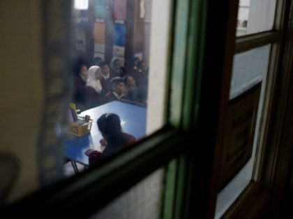 "LONDON, UNITED KINGDOM: WITH ""RELIGIOUS EDUCATION A FESTIVAL OF LIGHT IN BRITAIN"" A young girl wearing a muslim headscarf listens to her teachers leason while in class at Featherstone Primary school 09 December2003 in Southall London. . Sitting cross-legged the children intone a Sikh chant accompanied by Punjabi instruments as …"
