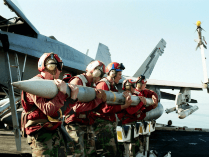 """396510 01: Aviation Ordnancemen Load An Aim-120 Advanced Medium-Range Air-To-Air Missile On The Wing Of An F/A-18 """"Hornet"""" Strike Fighter October 24, 2001 Aboard The Aircraft Carrier USS Theodore Roosevelt. The Roosevelt Is Conducting Missions In Support Of Operation Enduring Freedom. (Photo By U.S. Navy/Getty Images)"""