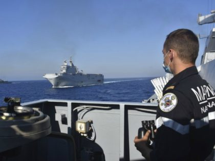 This photo provided Friday Aug.14, 2020 by the French Defense Ministry shows the French Tonnerre helicopter carrier, center, escorted by Greek and French military vessels during a maritime exercise in the Eastern Mediterranean, Thursday, Aug. 13, 2020. Greece's prime minister warmly thanked France Thursday for boosting its military presence in …