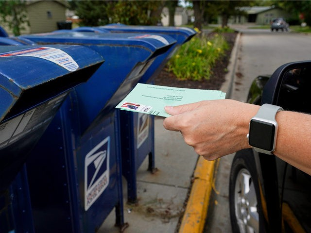 A person drops into a mail box applications for mail-in ballots, in Omaha, Neb., Tuesday, Aug. 18, 2020. The Postmaster general announced Tuesday he is halting some operational changes to mail delivery that critics warned were causing widespread delays and could disrupt voting in the November election. Postmaster General Louis …