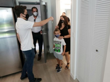 Sixteen-year-old Steven Ferreiro, left, founder of the local non-profit Helping Others and Giving Hope, hands over keys to a new apartment to Ayleen Apathy, right, as her son Vaughn, 7, second from right, and Alex Ballina, second from left, director of asset management for AHS Residential real estate development company, …