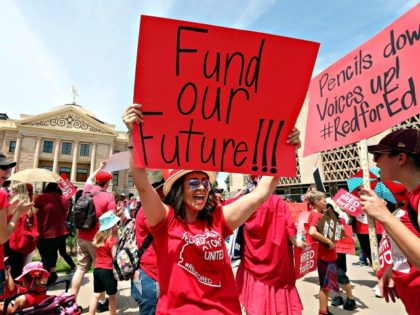 PHOENIX, AZ - APRIL 26: An Arizona teacher holds up a sign in front of the State Capitol during a #REDforED rally on April 26, 2018 in Phoenix, Arizona. Teachers state-wide staged a walkout strike on Thursday in support of better wages and state funding for public schools. (Photo by …