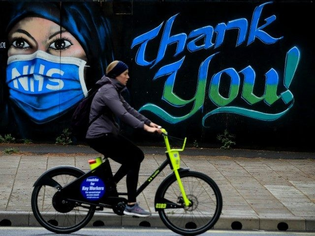 LONDON, ENGLAND - APRIL 29: A woman cycles past a piece of street art, created by The Artful Dodger, thanking the NHS on April 29, 2020 in London, England. British Prime Minister Boris Johnson, who returned to Downing Street this week after recovering from Covid-19, said the country needed to …