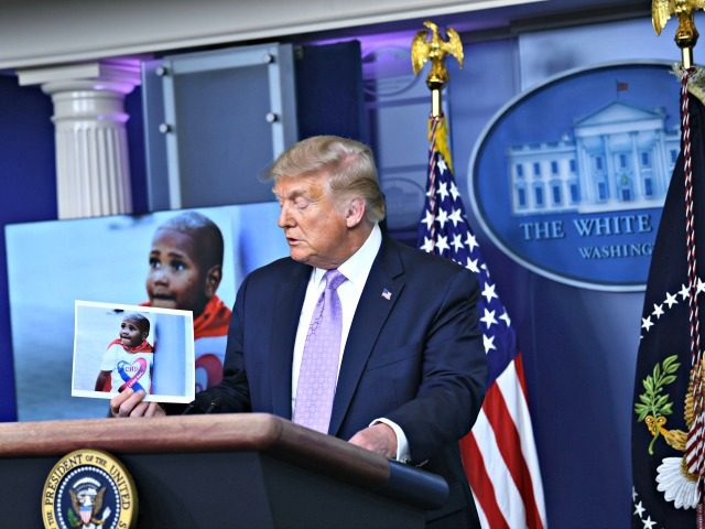 US President Donald Trump holds up a photo of LeGend Taliferro, a victim of a crime during a news conference in the Brady Briefing Room of the White House in Washington, DC, on August 13, 2020. (Photo by Brendan Smialowski / AFP) (Photo by BRENDAN SMIALOWSKI/AFP via Getty Images)