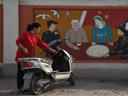 This photo taken on June 2, 2019 shows a Uighur woman beside a propaganda painting showing soldiers meeting with a Uighur family, outside a military hospital near Kashgar in China's northwest Xinjiang region. - China has enforced a massive security crackdown in Xinjiang, where more than one million ethnic Uighurs …