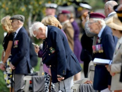 ALREWAS, UNITED KINGDOM - AUGUST 15: Veterans and family members observe a moments silence during a national service of remembrance, marking the 75th Anniversary of VJ Day, at The National Memorial Arboretum on August 15, 2020 in Alrewas, Staffordshire, England. (Photo by Anthony Devlin-WPA Pool/Getty Images)