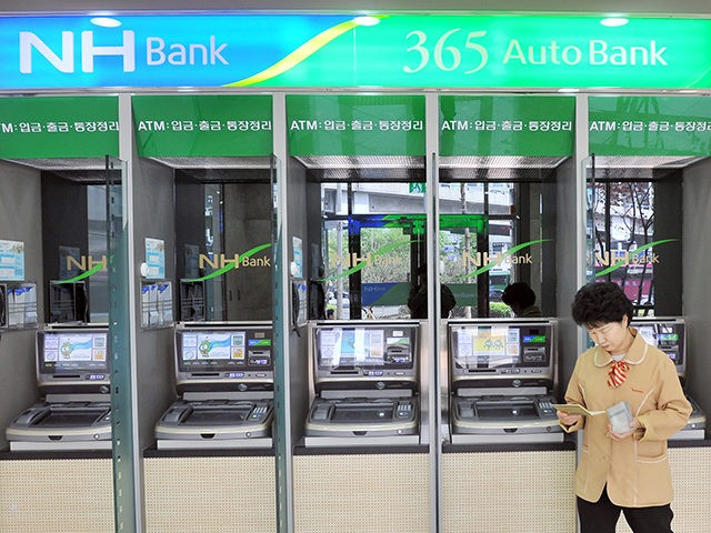 A South Korean woman looks at her bankbook in front of automated-teller machines of the National Agricultural Cooperative Federation, or NongHyup, in Seoul on May 3, 2011. North Korea was to blame for a cyber-attack that paralysed operations at one of South Korea's largest banks last month, prosecutors said. AFP …