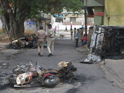 """Policemen walk past burnt vehicles in Bangalore on August 12, 2020, after violence broke out overnight in Devara Jevana Halli area following a """"derogatory"""" Facebook post about the Prophet Mohammed that sparked riots. - Two people died after a """"derogatory"""" Facebook post about the Prophet Mohammed sparked riots in India's …"""