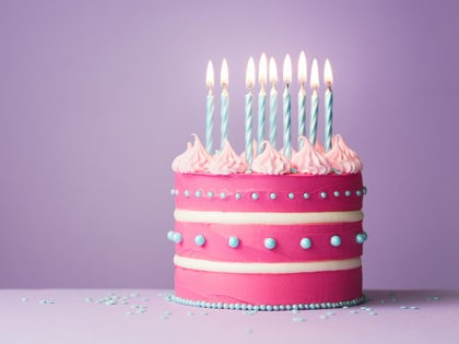 Pink birthday cake with nine candles