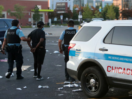 CHICAGO, ILLINOIS - AUGUST 10: Police officers detain a man who was found inside of a Best Buy store after parts of the city had widespread looting and vandalism, on August 10, 2020 in Chicago, Illinois. Police made several arrests during the night of unrest and recovered at least one …