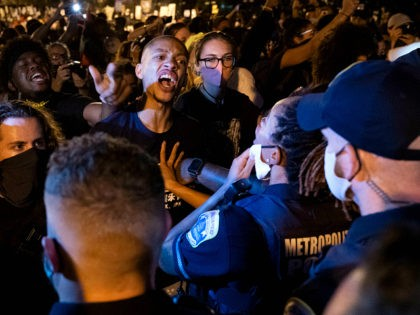 Demonstrators confront police officers during a rally to protest US President Donald Trump's acceptance of the Republican National Convention nomination at Black Lives Matter plaza across from the White House on August 27, 2020 in Washington, DC. - President Donald Trump accepts the Republican Party nomination for reelection tonight, August …