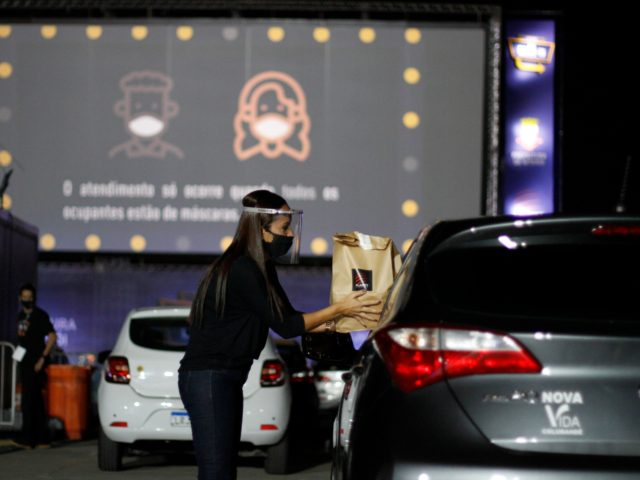 NITEROI, BRAZIL - JUNE 25: An employee delivers food to a moviegoer through the car window at a drive-in cinema at Caminho Niemeyer amidst the coronavirus (COVID-19) pandemic on June 25, 2020 in Niteroi, Brazil. The space has a capacity for up to 110 vehicles, and a 210 square meter …