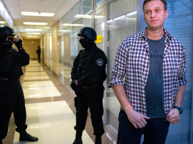 In this Thursday, Dec. 26, 2019 file, Russian opposition leader Alexei Navalny speaks to the media in front of security officers standing guard at the Foundation for Fighting Corruption office in Moscow, Russia. Navalny on Monday, July 20, 2020 announced the closure of his non-profit Anti-Corruption Foundation (FBK) over the …