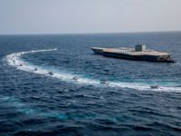 In this photo released Tuesday, July 28, 2020, by Sepahnews, Revolutionary Guard's speed boats circle around a replica aircraft carrier during a military exercise. Iran's paramilitary Revolutionary Guard has fired a missile from a helicopter targeting the mock-up aircraft carrier in the strategic Strait of Hormuz according to footage aired …