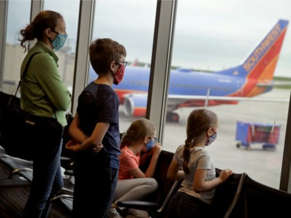 A family wearing masks waits to board a Southwest Airlines flight Sunday, May 24, 2020 at Kansas City International airport in Kansas City, Mo. About three dozen passengers boarded the plane with a capacity of nearly 150 as people are opting not to travel on the normally busy Memorial Day …