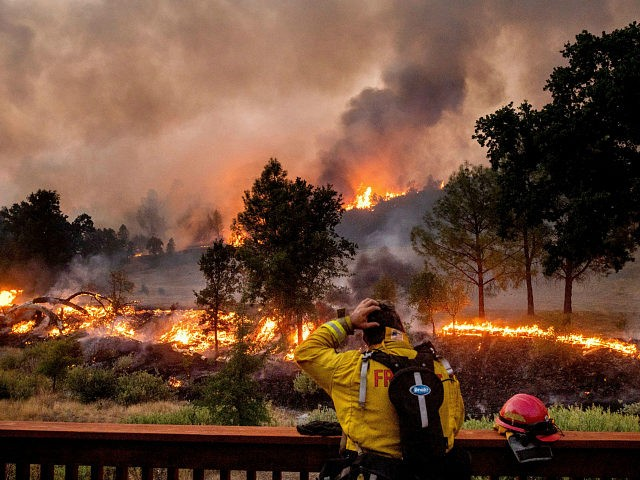 A firefighter rubs his head while watching the LNU Lightning Complex fires spread through the Berryessa Estates neighborhood of unincorporated Napa County, Calif., on Friday, Aug. 21, 2020. The blaze forced thousands to flee and destroyed hundreds of homes and other structures. (AP Photo/Noah Berger)