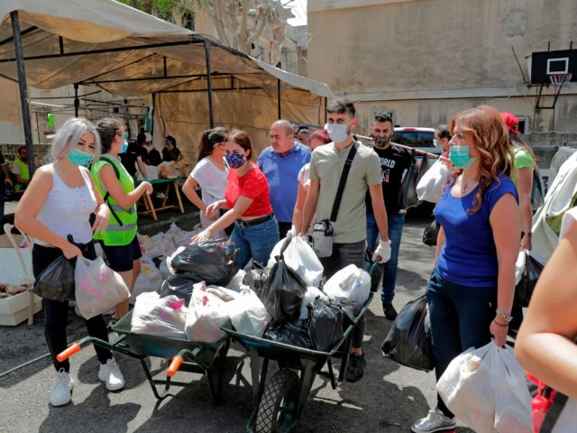 Lebanese volunteers distribute food in the Karantina neighbourhood near Beirut's port on August 11, 2020 following a huge chemical explosion that devastated large parts of the Lebanese capital. (Photo by ANWAR AMRO / AFP) (Photo by ANWAR AMRO/AFP via Getty Images)