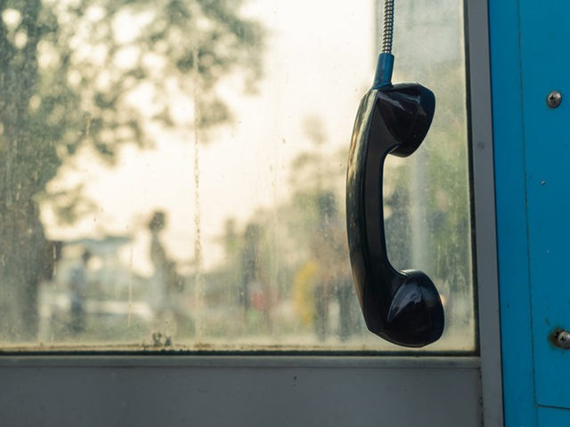 Telephone receiver hanging in phone booth