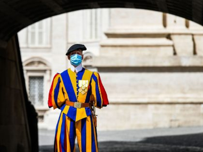 A Swiss Guard wearing a face mask stands guard by St. Peter's Basilica as it reopens on May 18, 2020 in The Vatican during the lockdown aimed at curbing the spread of the COVID-19 infection, caused by the novel coronavirus. - Saint Peter's Basilica throws its doors open to visitors …