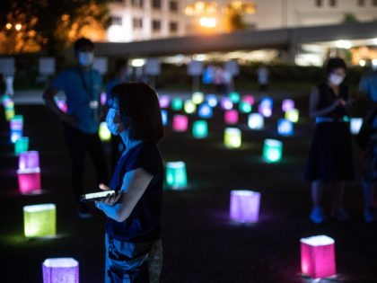 A visitor watches a screen (not pictured) displaying virtual lanterns as paper lanterns are placed to mark the 75th anniversary of the atomic bombing, at a park in in Hiroshima on August 6, 2020. - Japan on August 6, 2020 marked 75 years since the world's first atomic bomb attack, …