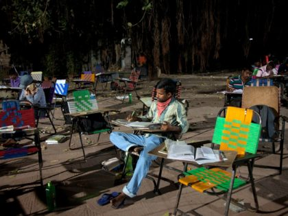 In this Friday, Feb. 17, 2017 photo, P. Venkateshwarlu, a 27-year old graduate preparing for a government accountant's job, studies in an open ground outside the City Central Library in Hyderabad, India. Hundreds of young college students and job-seekers, armed with their books and other study material sit and prepare …