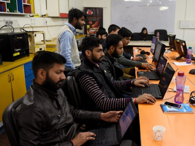 In this photograph taken on February 6, 2017, employees of Indian company Nuts and Boltz work in their office in New Delhi. Since coming to power in 2014, Narendra Modi has been looking to overhaul India's image as an awkward country in which to do business and instead emulate China …