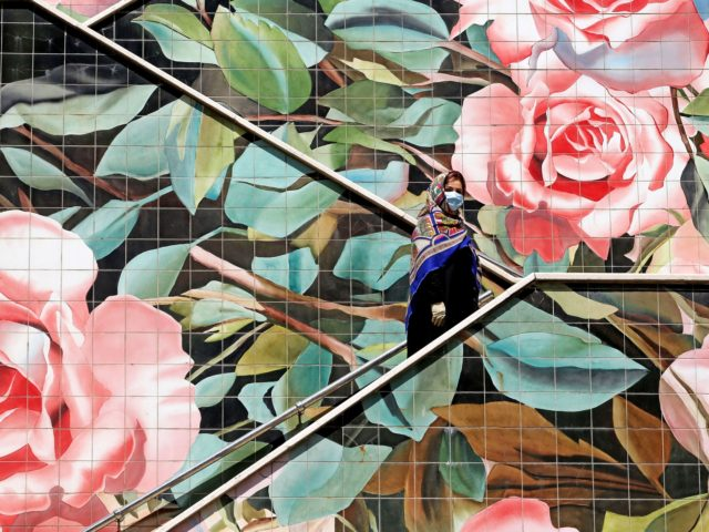 An Iranian woman wearing a protective mask due to the COVID-19 pandemic, climbs up a decorated stairway in the capital Tehran, on July 14, 2020. (Photo by ATTA KENARE / AFP) (Photo by ATTA KENARE/AFP via Getty Images)
