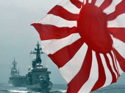 The flag of the Japanese Maritime Self-Defense Force (MSDF) flutters in the wind while MSDF escorts ship Kurama (R) and Hyuga (L) make its fleet review off Sagami Bay, Japan's Kanagawa prefecture on October 14, 2012. AFP PHOTO / KAZUHIRO NOGI (Photo credit should read KAZUHIRO NOGI/AFP/GettyImages)